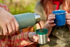 Duas mulheres que apreciam o café quente em uma caminhada Fotografia de Stock Royalty Free