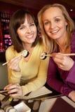 Duas mulheres que apreciam o sushi no restaurante fotografia de stock royalty free