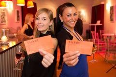 Duas mulheres que apresentam bilhetes do teatro ou do filme Fotos de Stock Royalty Free