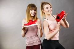 Duas mulheres que apresentam a instrutores do sportswear sapatas fotografia de stock