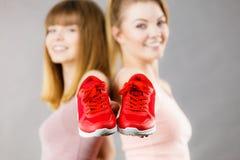 Duas mulheres que apresentam a instrutores do sportswear sapatas imagens de stock
