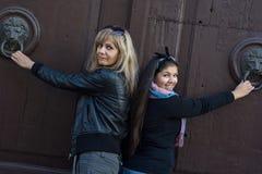 Duas mulheres que batem na porta com aldravas Foto de Stock Royalty Free