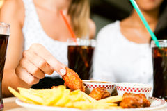 Duas mulheres que comem as asas de galinha e que bebem a soda Foto de Stock