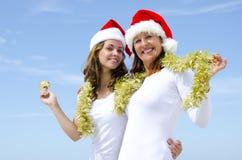 Duas mulheres que comemoram o feriado ensolarado do Natal Foto de Stock