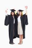 Duas mulheres que comemoram sua graduação fotografia de stock