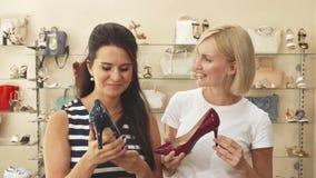 Duas mulheres que comparam sapatas na sapataria video estoque