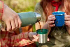 Duas mulheres que compartilham de uma garrafa térmica do café Imagens de Stock