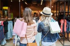Duas mulheres que compram na frente do boutique