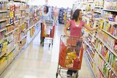 Duas mulheres que compram no supermercado imagens de stock
