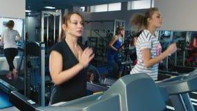 Duas mulheres que correm na escada rolante no gym video estoque