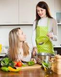 Duas mulheres que cozinham algo com vegetais fotografia de stock