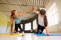 Duas mulheres que dão a prancha de execução da elevação cinco no gym fotos de stock royalty free