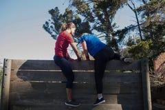Duas mulheres que escalam uma parede de madeira durante o treinamento do curso de obstáculo imagens de stock royalty free