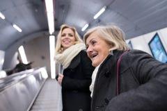 Duas mulheres que estão na escada rolante no metro de Viena fotos de stock royalty free