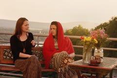 Duas mulheres que falam no balcão no por do sol Imagem de Stock