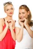 Duas mulheres que fazem a forma do coração amam o símbolo com mãos Foto de Stock Royalty Free