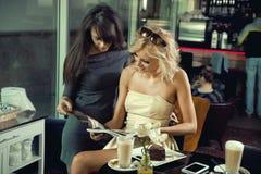 Duas mulheres que lêem um jornal fotografia de stock