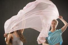Duas mulheres que lanç a tela cor-de-rosa no estúdio fotografia de stock