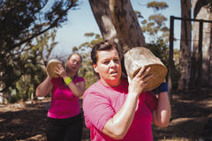 Duas mulheres que levam um log de madeira pesado durante o curso de obstáculo imagens de stock