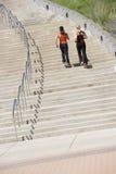 Duas mulheres que movimentam-se acima das etapas Fotografia de Stock Royalty Free