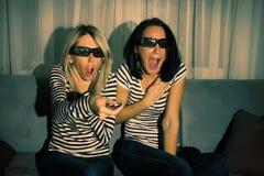 Duas mulheres que olham o filme 3D em casa Fotografia de Stock