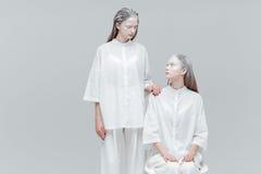 Duas mulheres que olham se na roupa branca foto de stock
