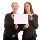 Duas mulheres que prendem um cartão em branco. Isolado no branco Fotografia de Stock Royalty Free