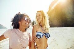 Duas mulheres que riem ao andar junto ao longo de um Sandy Beach foto de stock royalty free