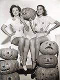 Duas mulheres que sentam-se na cerca com abóboras cinzeladas Imagens de Stock