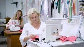 Duas mulheres que sentam-se nas tabelas que trabalham na fabricação de roupa Mulher que costura o pano cor-de-rosa na máquina mod filme