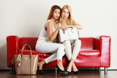 Duas mulheres que sentam-se no sofá que apresenta o saco fotografia de stock