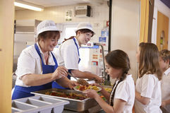 Duas mulheres que servem o alimento a uma menina em uma fila do bar de escola fotografia de stock