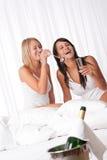 Duas mulheres que têm o divertimento no quarto do hotel de luxo fotos de stock royalty free
