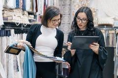 Duas mulheres que trabalham com a tabuleta digital das telas interiores na sala de exposições para cortinas e telas de estofament fotos de stock royalty free