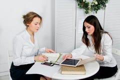 Duas mulheres que trabalham junto no escritório branco Foto de Stock Royalty Free