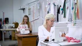 Duas mulheres que trabalham na fabricação de roupa Mulher no terno branco que senta-se no primeiro plano e que costura o pano cor video estoque