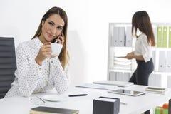 Duas mulheres que trabalham no escritório Um deles está refrigerando para fora Imagens de Stock Royalty Free