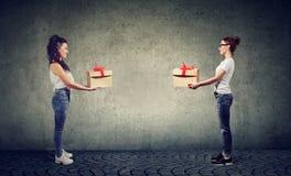 Duas mulheres que trocam com as caixas de presente que olham felizmente em se imagens de stock royalty free