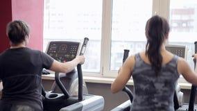 Duas mulheres são contratadas em máquinas do exercício no gym Trenerovka das mulheres As meninas fazem exercícios em uma janela e video estoque