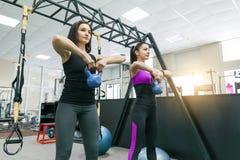 Duas mulheres saudáveis novas que fazem exercícios com peso no gym Aptidão, esporte, treinamento, pessoa, conceito saudável do es imagens de stock