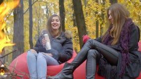 Duas mulheres sentam-se em sopros sentam-se perto do fogo, um deles têm uma garrafa térmica video estoque
