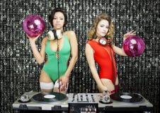 Duas mulheres 'sexy' bonitas do DJ do disco nos biquinis que executam em um clu Fotos de Stock Royalty Free