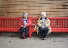 Duas mulheres superiores felizes que conversam em um banco vermelho fora Imagens de Stock Royalty Free