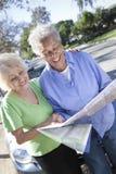 Duas mulheres superiores felizes que leem o mapa fotos de stock royalty free