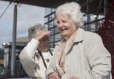 Duas mulheres superiores que falam e que riem fora fotos de stock royalty free