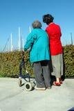 Duas mulheres uma com um caminhante Fotos de Stock Royalty Free