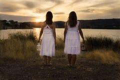 Duas mulheres vestidas no branco que olha o por do sol foto de stock