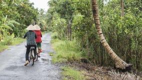 Duas mulheres vietnamianas montam suas bicicletas em uma estrada do campo no delta de Mekong fotos de stock royalty free