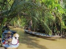 Duas mulheres vietnamianas têm o almoço que senta-se em um barco de madeira Estando em um outro barco e conduzindo uma pá, um hom imagem de stock