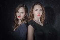 Duas namoradas consideráveis que estão junto de volta à parte traseira olhando a câmera Estúdio disparado no estilo noir Fotos de Stock